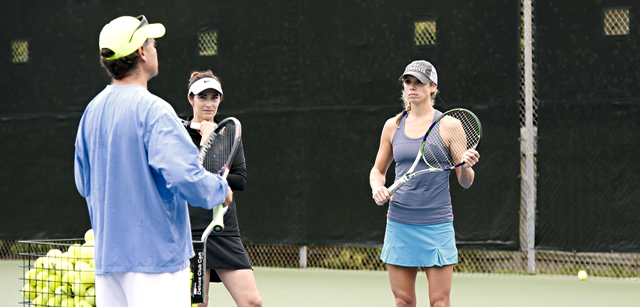 tennis coach instructing adults